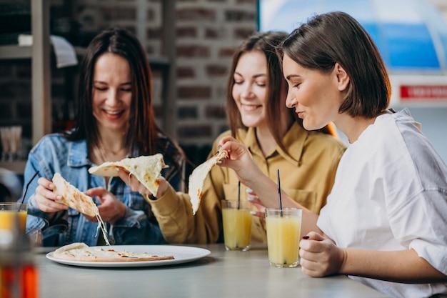 Tre ragazze che mangiano pizza in un bar Foto Gratuite