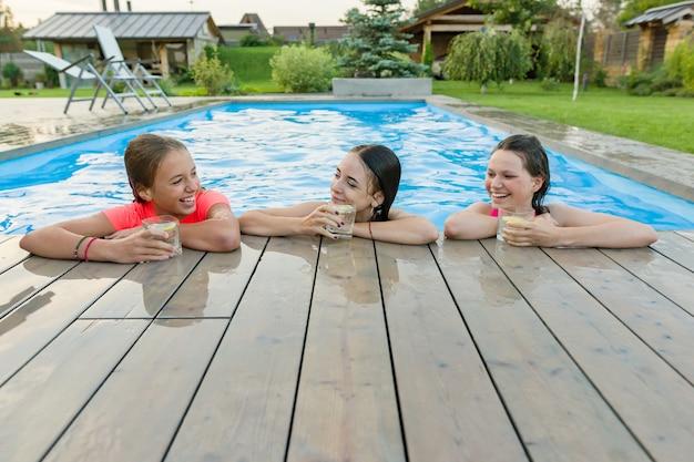 Tre ragazze felici con bevande sulla festa d'estate in piscina Foto Premium