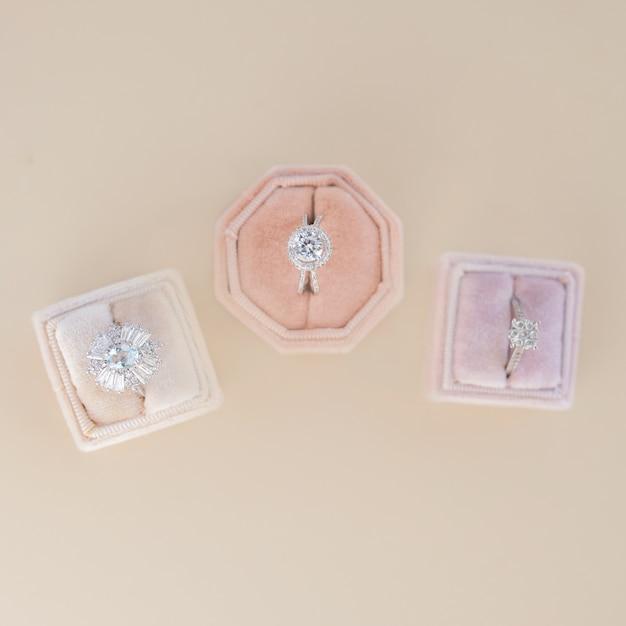 Tre scatole con anelli di fidanzamento si ergono su un tavolo beige Foto Gratuite