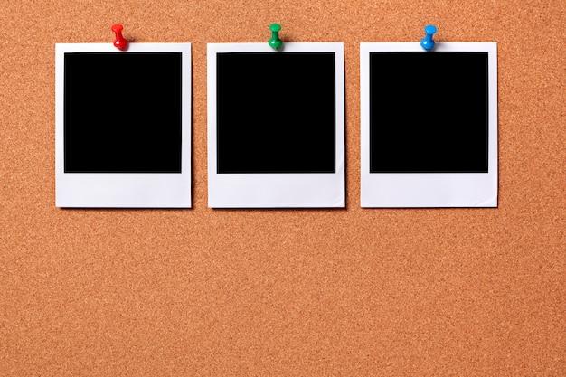 Tre stampe fotografiche polaroid appuntate ad una bacheca di sughero Foto Gratuite