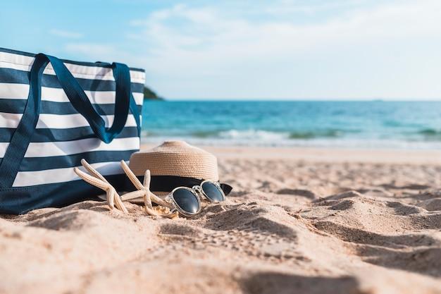 Tre stelle marine con borsa blu sulla sabbia Foto Gratuite