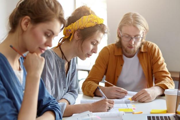 Tre studenti seduti insieme sul posto di lavoro, scrivendo con le matite e studiando letteratura scientifica, preparandosi per gli esami all'università. ragazzo barbuto e due femmine che lavorano al progetto Foto Gratuite
