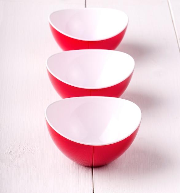 Tre tazze rosse vuote su una tavola di legno bianca Foto Premium