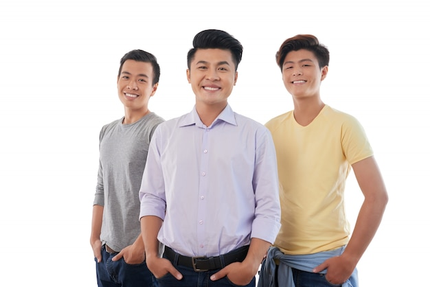 Tre uomini asiatici in piedi con le mani in tasca e sorridente per la fotocamera Foto Gratuite