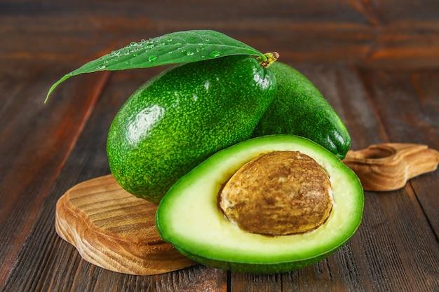 Tre verdi avocado maturi crudi e un mezzo tagliato con un osso con foglie Foto Premium