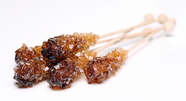 Tre zucchero candito su un bastone su sfondo bianco Foto Gratuite