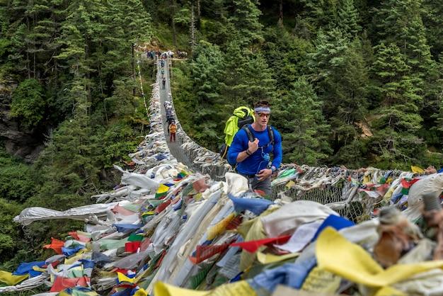 Trekker che attraversano un ponte sospeso nella regione di everest, nepal. Foto Premium