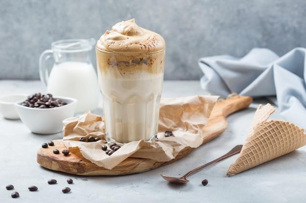 Trend alimentare - caffè dalgona, bevanda istantanea montata su fondo rustico Foto Premium