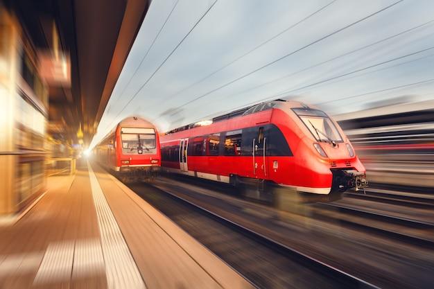 Treni passeggeri rossi ad alta velocità moderni al tramonto. stazione ferroviaria Foto Premium