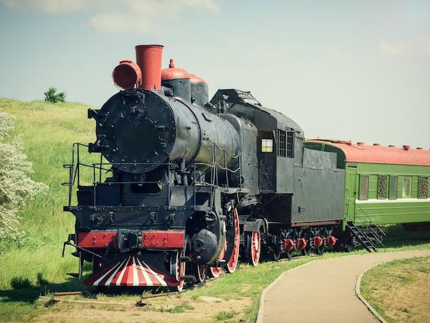 Treno d'annata classico con un'automobile verde sulle piste nel giorno di estate. Foto Premium