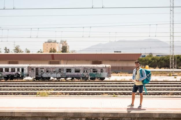 Treno sorridente aspettante dell'uomo a lungo girato Foto Gratuite