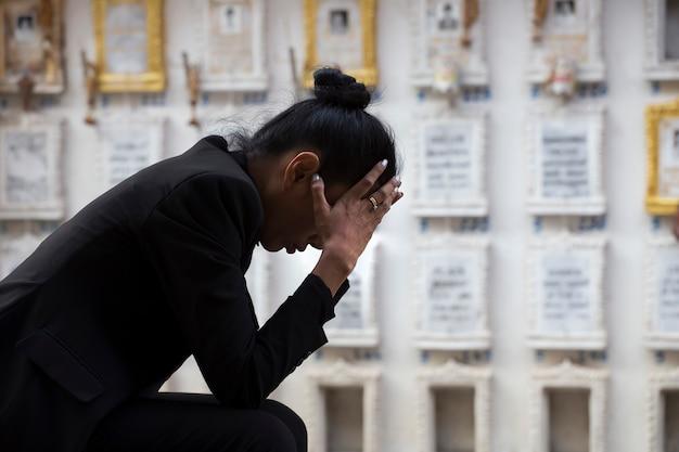 Triste donna seduta vicino a una tomba Foto Premium