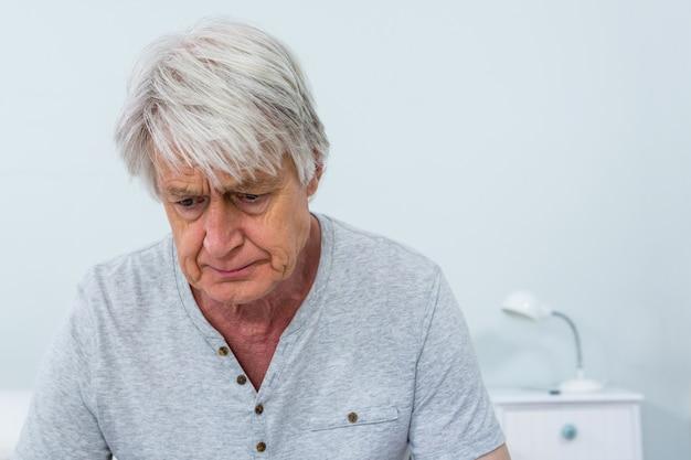 Triste uomo anziano seduto a casa Foto Premium