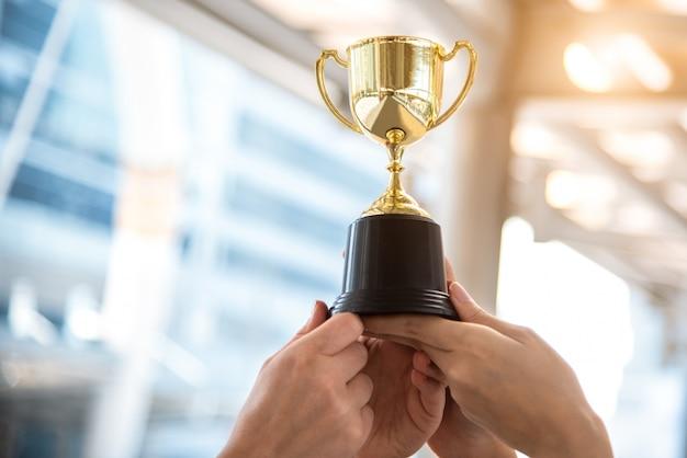Trofeo d'oro campione per il vincitore con le mani del giocatore sportivo nello stadio sportivo Foto Premium