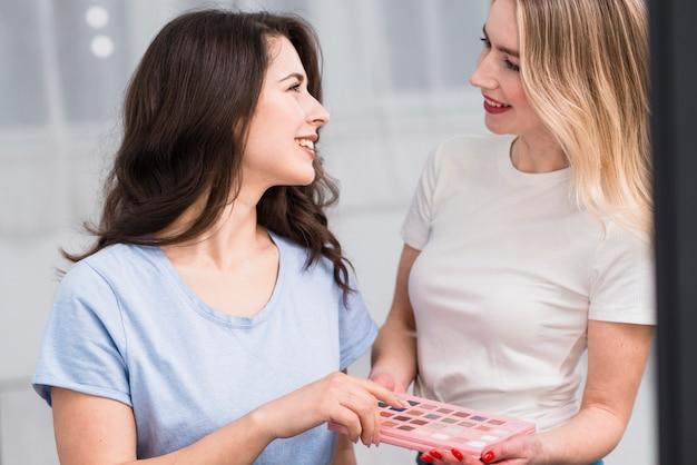 Truccatore femminile con il cliente che sceglie ombretto Foto Gratuite