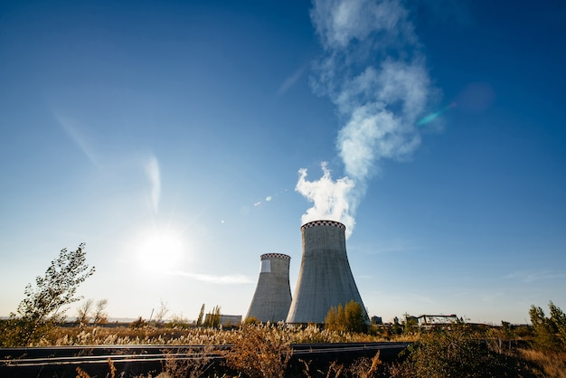 Tubi di fumo della centrale elettrica termica contro cielo blu Foto Premium