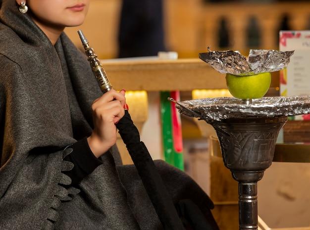 Tubo del narghilé della tenuta della donna che si siede al salotto di shisha Foto Gratuite