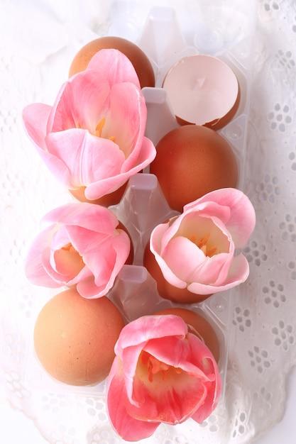 Tulipani della decorazione di pasqua della primavera in gusci d'uovo su un pizzo delicato del fondo bianco Foto Premium