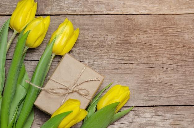 Tulipani e contenitore di regalo gialli su fondo di legno Foto Premium