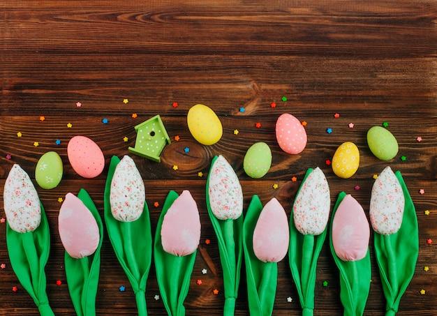 Tulipani fatti a mano e uova di pasqua su fondo in legno Foto Premium
