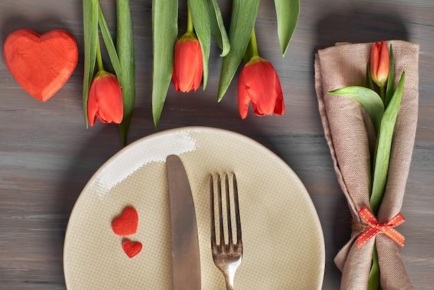 Tulipani freschi e decorazioni cuore su grigio Foto Premium