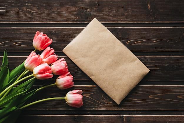 Tulipani rosa dei fiori con una busta postale di carta su una tavola rustica di legno Foto Premium
