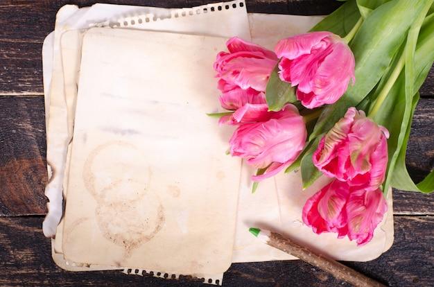 Tulipani rosa e carta vintage, matita su un fondo di legno. spazio libero per il tuo testo. Foto Premium