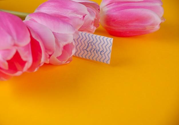 Tulipani rosa su sfondo giallo con nota amore lettera d'amore Foto Premium
