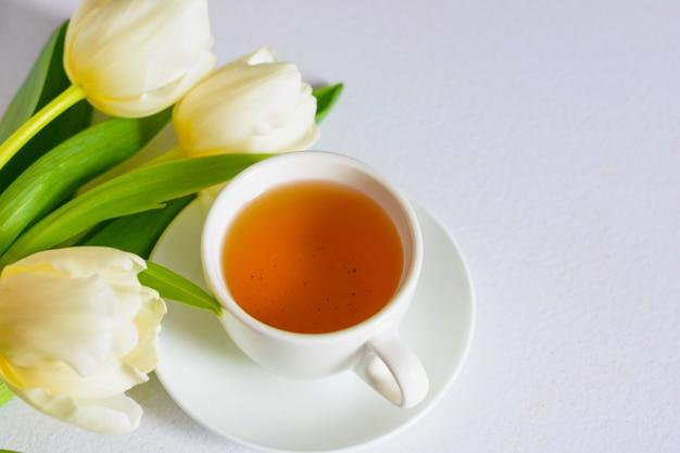 Tulipani teneri bianchi della molla e una tazza di tè su fondo bianco Foto Premium