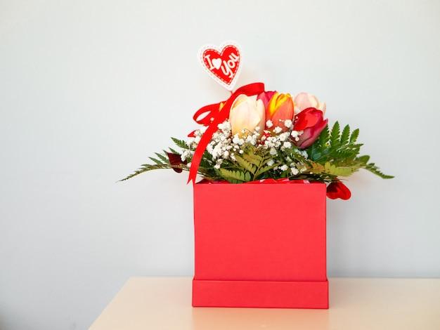 Tulipano nel contenitore di regalo su fondo bianco. fiori di primavera. tulipani multicolori in una scatola rossa. Foto Premium