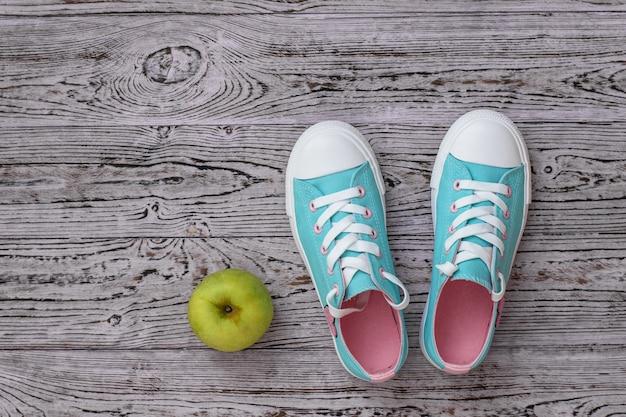 Turchese con scarpe da ginnastica rosa e una mela sul pavimento di legno. Foto Premium