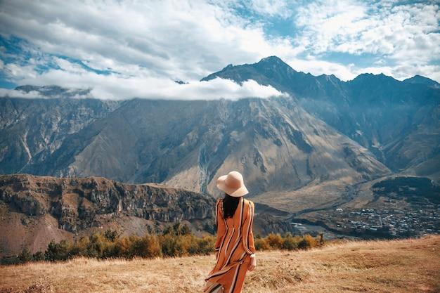 Turista all'aperto della donna di stile di vita di viaggio che posa sulle montagne e sul cielo nuvoloso. Foto Premium