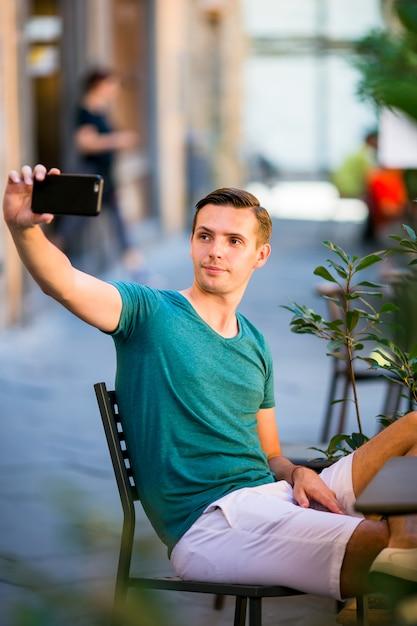Turista caucasico con lo smartphone che prende selfie che si siede in caffè all'aperto. giovane ragazzo urbano in vacanza alla scoperta della città europea Foto Premium