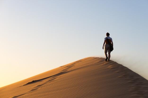 Turista che cammina sulle dune di sabbia a sossusvlei, deserto del namib. viaggiare, avventura e vacanze in africa. Foto Premium