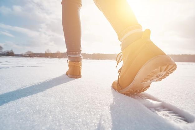 Turista che cammina via attraverso la neve al tramonto Foto Premium