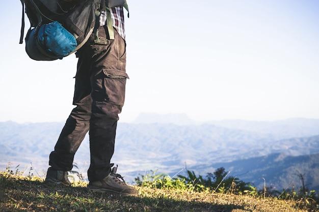 Turista dalla cima della montagna. i raggi del sole. l'uomo indossa un grande zaino contro la luce del sole Foto Gratuite