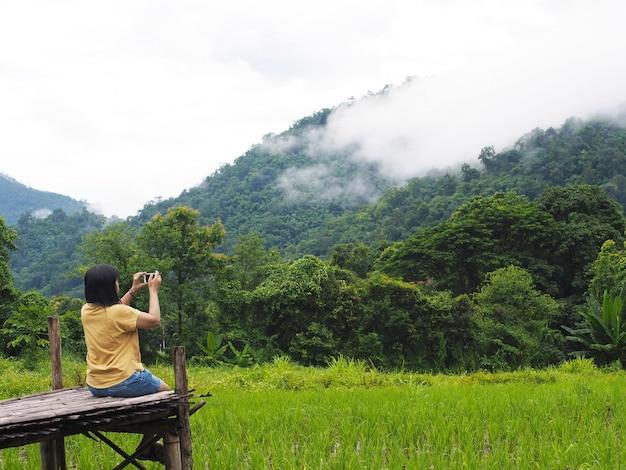 Turista della donna che si siede sul sentiero per pedoni di legno e che prende fotografia della montagna e del giacimento del riso Foto Premium