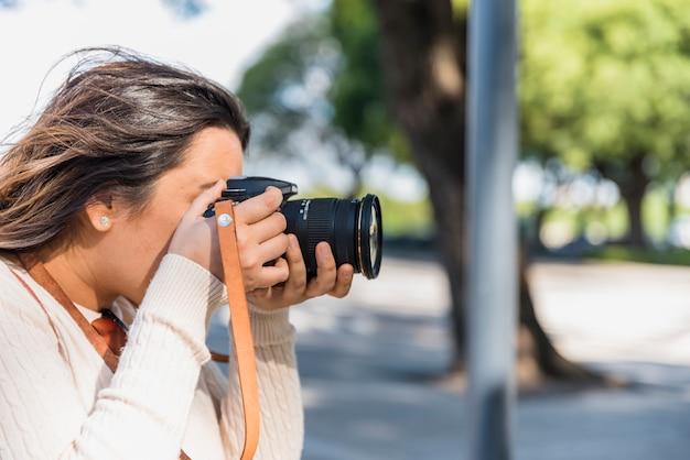 Turista femminile che fotografa dalla macchina fotografica professionale all'aperto Foto Gratuite