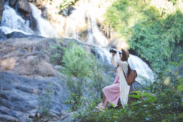 Turista femminile che sta guardando il binocolo per vedere l'atmosfera della cascata Foto Gratuite