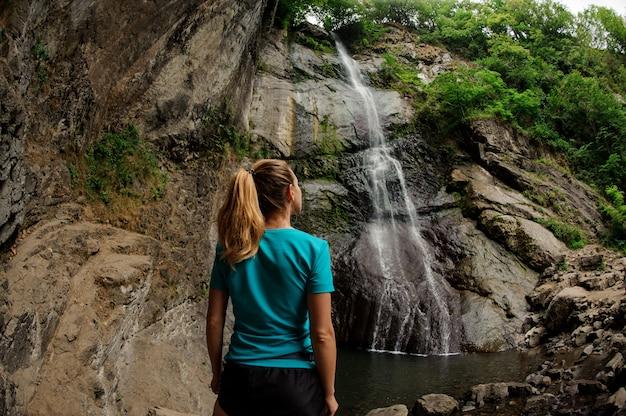 Turista femminile in abiti sportivi in piedi vicino alla cascata Foto Premium