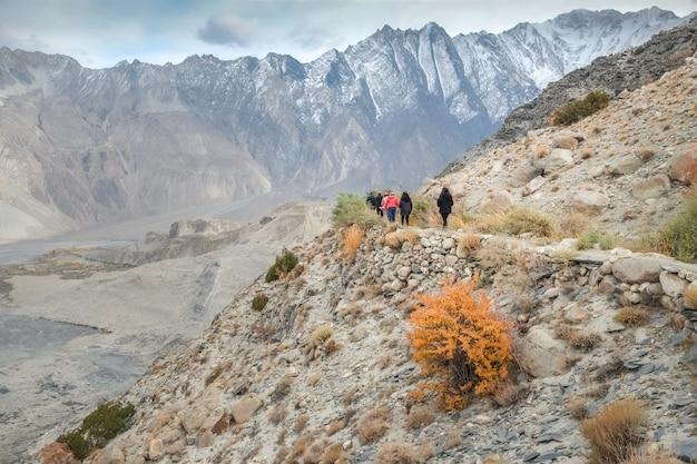 Turisti che camminano lungo il sentiero tra la catena montuosa del karakoram Foto Premium