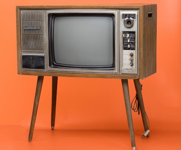 Tv vintage isolato su sfondo arancione. Foto Premium