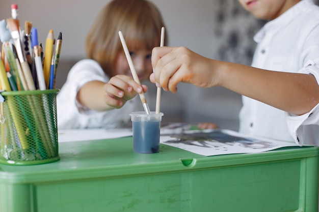 Ubicazione dei bambini al tavolo verde e disegno Foto Gratuite
