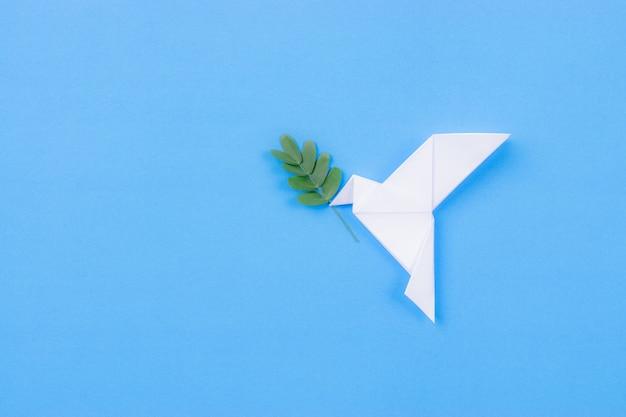 Uccello bianco fatto dal ramo di foglia di trasporto di carta Foto Premium
