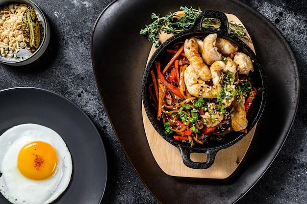 Udon mescolare gli spaghetti con pollo e verdure in padella. sfondo nero. vista dall'alto Foto Premium