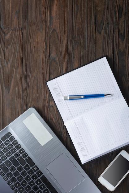 Ufficio a casa. ufficio di quarantena. computer portatile e blocco note sulla scrivania. vista piana, vista dall'alto. Foto Premium