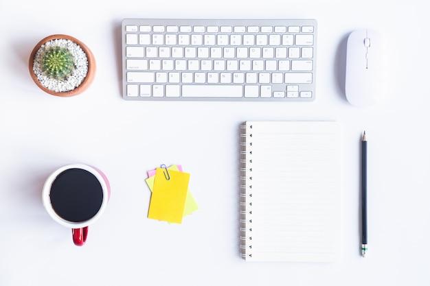 Ufficio bianco scrivania con laptop, smartphone e altre forniture di lavoro con una tazza di caffè Foto Premium