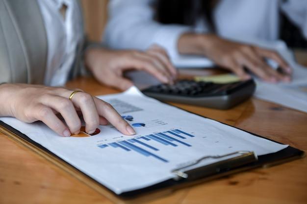 Ufficio della ragazza utilizzando una calcolatrice per analisi di grafici. Foto Premium
