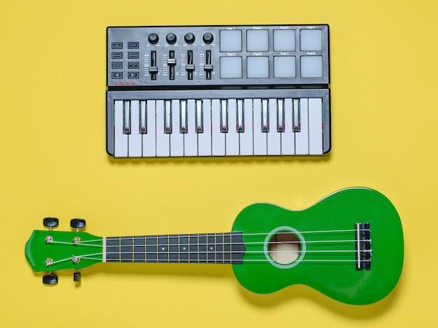 Ukulele e miscelatore verdi di musica su fondo giallo. la vista dall'alto. Foto Premium