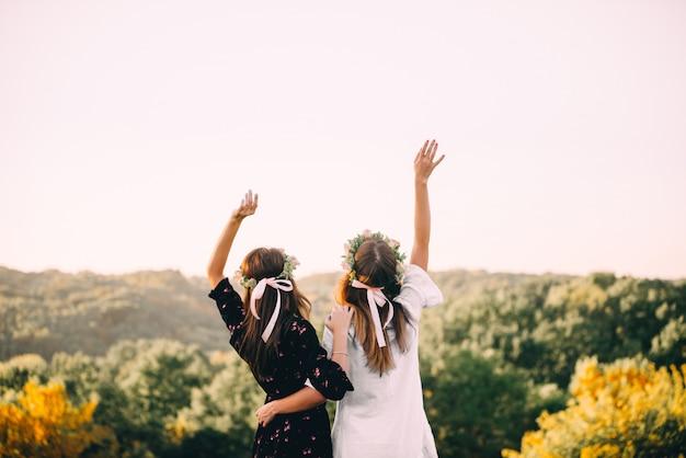 Un abbraccio di due ragazze durante il tramonto nel campo con il concetto di amicizia di vetri di vino Foto Premium